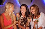 Laughing women drinking cocktails in nightclub Stock Photo - Premium Royalty-Free, Artist: Blend Images, Code: 6113-06498664