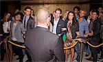Crowd gesturing to bouncer behind rope outside night club Stock Photo - Premium Royalty-Free, Artist: Ikon Images, Code: 6113-06498667