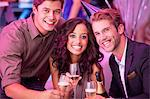 Portrait of smiling friends drinking champagne in nightclub Stock Photo - Premium Royalty-Free, Artist: Blend Images, Code: 6113-06498679