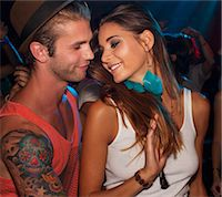 flirting - Close up of smiling couple face to face in nightclub Stock Photo - Premium Royalty-Freenull, Code: 6113-06498697