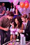 Smiling friends drinking champagne and celebrating birthday in nightclub Stock Photo - Premium Royalty-Free, Artist: Blend Images, Code: 6113-06498700