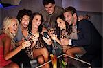 Smiling friends drinking cocktails and looking down at cell phone in nightclub Stock Photo - Premium Royalty-Free, Artist: Blend Images, Code: 6113-06498703