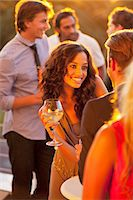 flirting - Smiling woman with wine glass talking to man on sunny balcony Stock Photo - Premium Royalty-Freenull, Code: 6113-06498711