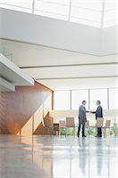 Businessmen shaking hands at circle of chairs in lobby Stock Photo - Premium Royalty-Freenull, Code: 6113-06498829