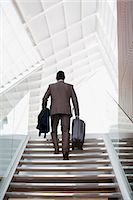 Businessman with suitcase ascending stairs Stock Photo - Premium Royalty-Freenull, Code: 6113-06498841