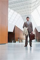 Portrait of smiling businessman holding coat and briefcase in lobby Stock Photo - Premium Royalty-Freenull, Code: 6113-06498870