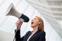 Businesswoman shouting into bullhorn Stock Photo - Premium Royalty-Freenull, Code: 6113-06498900