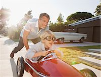 pushing - Father pushing son in go cart Stock Photo - Premium Royalty-Freenull, Code: 6113-06498924