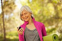 Older woman using cell phone outdoors Stock Photo - Premium Royalty-Freenull, Code: 6113-06499079