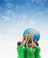 Team in green t-shirts lifting globe overhead Stock Photo - Premium Royalty-Freenull, Code: 6113-06499152