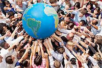 Crowd of people reaching for globe Stock Photo - Premium Royalty-Freenull, Code: 6113-06499191