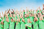 Crowd in green t-shirts cheering with arms raised Stock Photo - Premium Royalty-Free, Artist: Blend Images, Code: 6113-06499210
