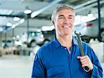 Portrait of smiling mechanic holding large wrench in auto repair shop Stock Photo - Premium Royalty-Free, Artist: Steve McDonough, Code: 618-06503951