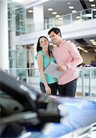 Smiling couple looking at car in car dealership showroom Stock Photo - Premium Royalty-Freenull, Code: 618-06503953