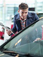 Smiling man with brochure looking at car in car dealership showroom Stock Photo - Premium Royalty-Freenull, Code: 618-06503956
