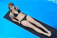 High Angle View of Young Woman Wearing Bikini Lying on Diving Board above Swimming Pool, Bavaria, Germany Stock Photo - Premium Rights-Managednull, Code: 700-06505720