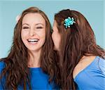 two young female friends whispering gossip - isolated on blue