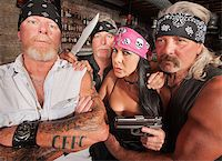 Four tough motorcycle gang members with weapons in tavern Stock Photo - Royalty-Freenull, Code: 400-06522839