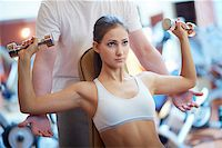 sweaty woman - Portrait of pretty girl training in gym with her trainer helping her Stock Photo - Royalty-Free, Artist: pressmaster, Code: 400-06524783