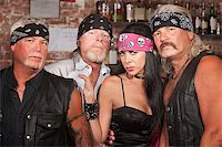 Tough male biker gang members with beautiful woman Stock Photo - Royalty-Freenull, Code: 400-06525848