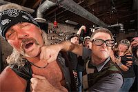 Confident geek punches mature biker gang man on chin Stock Photo - Royalty-Freenull, Code: 400-06525854