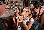 Female geek puts up fist to tough man in bar Stock Photo - Royalty-Free, Artist: creatista, Code: 400-06525855
