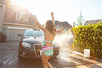 preteen swimsuit - Young girl dances while family washes their car in the driveway of their home on a sunny summer afternoon in Portland, Oregon, USA Stock Photo - Premium Royalty-Freenull, Code: 600-06531440