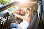 Young girl sitting in driver's seat of car, pretending to be old enough to drive as her smiling father watches on on a sunny summer evening in Portland, Oregon, USA Stock Photo - Premium Royalty-Free, Artist: Ty Milford, Code: 600-06531445