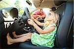 Little girl sitting in Driver's seat of car, pretending to be old enough to drive as her smiling father watches on on a sunny summer evening in Portland, Oregon, USA Stock Photo - Premium Royalty-Free, Artist: Ty Milford, Code: 600-06531448