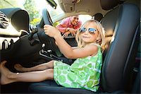 Portrait of little girl sitting in driver's seat of car, pretending to be old enough to drive as her smiling father watches on on a sunny summer evening in Portland, Oregon, USA Stock Photo - Premium Royalty-Freenull, Code: 600-06531449
