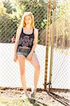 Portrait of young woman standing in front of chain link fence in park near the tennis court on a warm summer day in Portland, Oregon, USA Stock Photo - Premium Royalty-Free, Artist: Ty Milford, Code: 600-06531455
