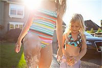 preteen bathing suit - Close-up of sisters washing car in driveway of their home on a sunny summer afternoon in Portland, Oregon, USA Stock Photo - Premium Royalty-Freenull, Code: 600-06531470