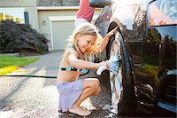 Young daughter helps father wash their car in the driveway of their home on a sunny summer afternoon in Portland, Oregon, USA Stock Photo - Premium Royalty-Freenull, Code: 600-06531473