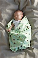 newborn baby girl in a white undershirt sleeping on a bed swaddled in a baby blanket, Ontario, Canada Stock Photo - Premium Royalty-Freenull, Code: 600-06531988