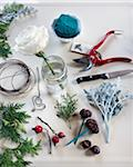 craft making materials such as a knife, floral sheers, floral wire, cedar, chestnuts, floral foam, white rose, and placecards on a white surface Stock Photo - Premium Royalty-Free, Artist: Yvonne Duivenvoorden, Code: 600-06531998