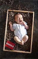 yawning newborn baby girl wearing white undershirt onesie in a shipping box labeled as fragile with packing paper Stock Photo - Premium Rights-Managednull, Code: 700-06532020