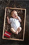 yawning newborn baby girl wearing white undershirt onesie in a shipping box labeled as fragile with packing paper Stock Photo - Premium Rights-Managed, Artist: Yvonne Duivenvoorden, Code: 700-06532020
