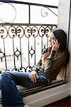 Woman on cell phone in windowsill Stock Photo - Premium Royalty-Free, Artist: Michael Mahovlich, Code: 649-06532535