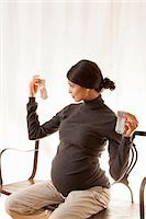 pregnant asian - Pregnant woman examining baby socks Stock Photo - Premium Royalty-Freenull, Code: 649-06532567