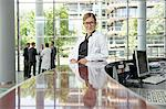 Doctor leaning on secretarys desk Stock Photo - Premium Royalty-Free, Artist: AWL Images, Code: 649-06532626