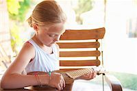 Girl strumming ukulele outdoors Stock Photo - Premium Royalty-Freenull, Code: 649-06532790