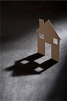 Cardboard house shape casting shadow Stock Photo - Premium Royalty-Freenull, Code: 649-06532934