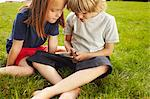 Children using cell phone in grass Stock Photo - Premium Royalty-Free, Artist: Blend Images, Code: 649-06533114