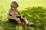 Boy tying his shoe in grass Stock Photo - Premium Royalty-Free, Artist: Blend Images, Code: 649-06533120