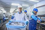 Worker holding bucket of fish in factory Stock Photo - Premium Royalty-Free, Artist: Blend Images, Code: 649-06533426