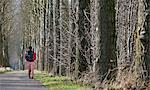 Woman walking on rural road Stock Photo - Premium Royalty-Free, Artist: Robert Harding Images, Code: 649-06533550