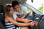A man leaning in car window helping his girlfriend with the GPS Stock Photo - Premium Royalty-Free, Artist: AlaskaStock              , Code: 653-06533733