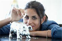 savings - Woman putting coin into piggy bank Stock Photo - Premium Royalty-Freenull, Code: 653-06534012
