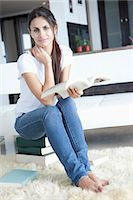 Woman at home sitting on books and reading Stock Photo - Premium Royalty-Freenull, Code: 653-06534025