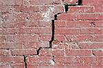 Close-up of a crack running through a red brick wall